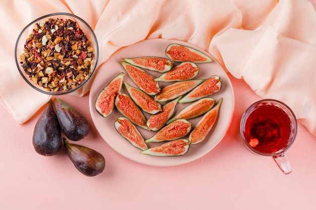 Vijgen met kopje thee, gedroogde kruiden in een bord op roze en textiel, plat lag.