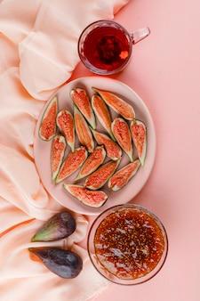 Vijgen met kopje thee in een bord op roze en textiel, bovenaanzicht.