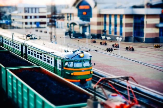 Vikhorevka, rusland - 26 april 2019: een treinstation gefotografeerd met een miniatuureffect. de trein- en kolenwagens staan vlakbij het perron.