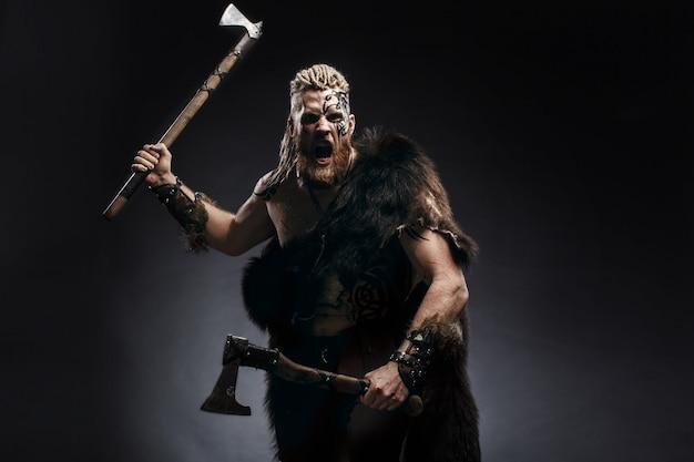 Viking gekleed in de huid van een beer die aanvalt met een bijl