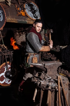 Viking smeedt wapens en zwaarden in de smederij. een man in krijgerskleren is in de smederij.