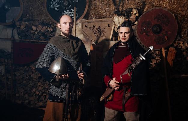 Vikingen poseren tegen het oude interieur van de vikingen.