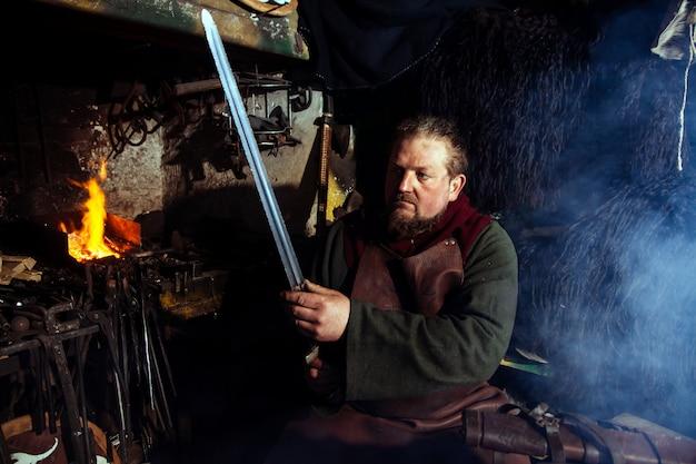 Vikingsmid smeedt wapens in de oude vintage smederij.