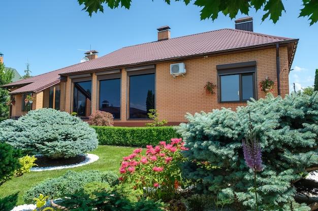 Villa in europese stijl met en tuin met mooi gesnoeide struiken voor het huis. landschapsontwerp. hoge kwaliteit foto