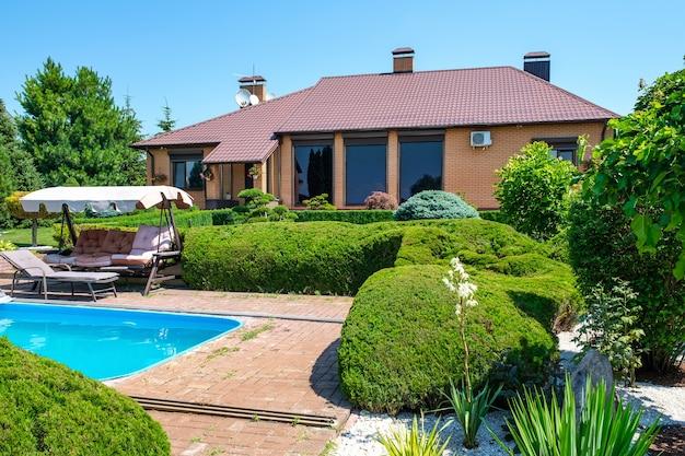 Villa in europese stijl met zwembad en tuin met mooi gesnoeide struiken en stenen voor het huis. landschapsontwerp. hoge kwaliteit foto