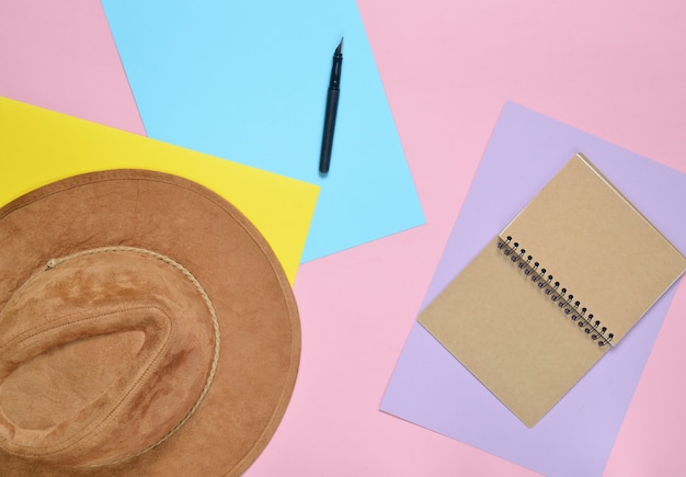 Vilten hoed, notebook, pen op gekleurd papier muur. het concept van reizen. minimalisme, bovenaanzicht