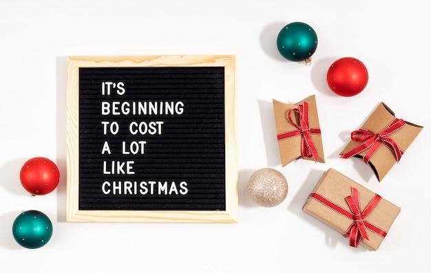 Vilten letterbord met grappige citaattekst het begint net als kerstmis veel te kosten. spemding geld op het dure concept van kerstmisgiften