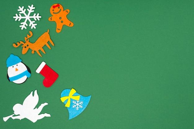 Vilten speelgoed voor het versieren van een kerstboom op een groene achtergrond met plaats voor tekst.