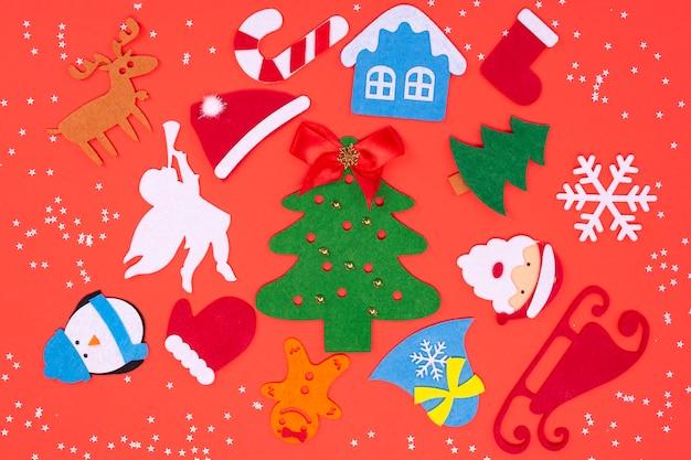 Vilten speelgoed voor het versieren van een kerstboom op een rode achtergrond.