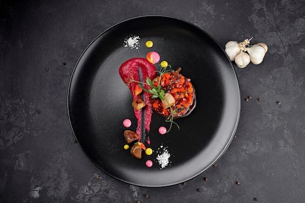 Vinaigrette salade op een zwarte achtergrond, op een zwarte plaat met knoflook