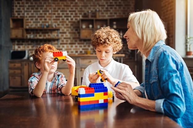 Vind je mijn auto leuk? selectieve focus op broers met krullend haar die naast elkaar zitten en creatief worden tijdens het spelen met een bouwdoos samen met hun zorgvuldige grootmoeder.