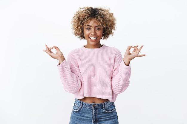 Vind je zen. ontspannen en vrolijke chill, knappe afro-amerikaanse vrouw die yoga beoefent, mediteert en glimlacht, bevrijd als staande in lotushouding met lichtbollen, nirvana bereikend over witte muur