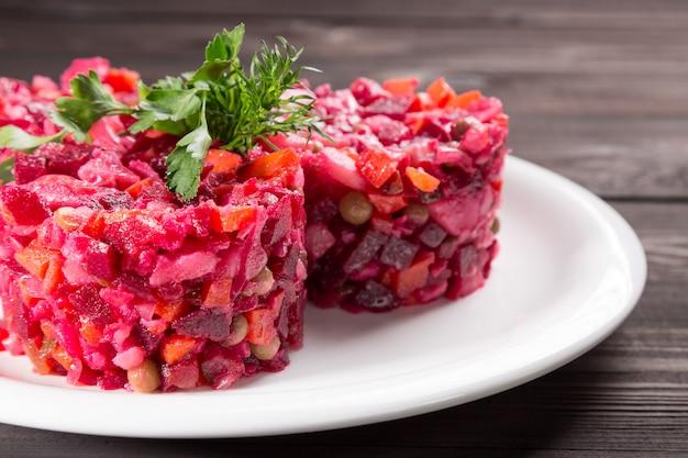Vinegret traditionele russische bietensalade en groenten met kruiden op witte plaat en houten lijst