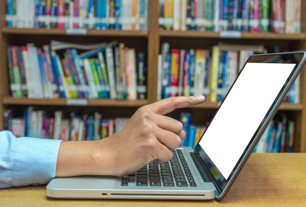 Vinger die op het scherm van laptop computer over de houten lijst in bibliotheek, onderwijs technolog richten