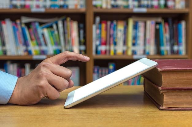 Vinger die op het scherm van tabletcomputer over de houten lijst in bibliotheek richten