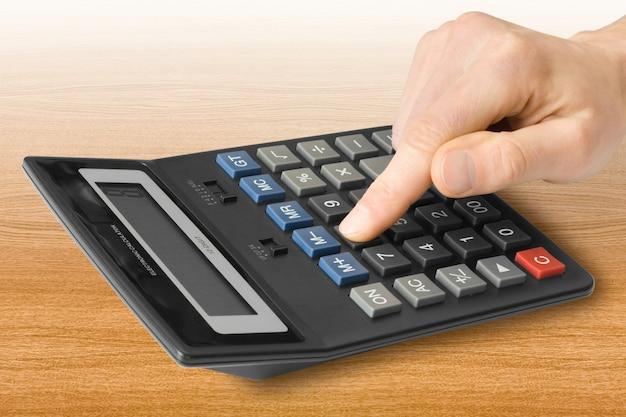 Vinger drukt op de knop op de rekenmachine