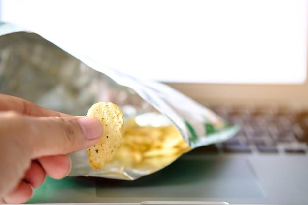 Vinger hand met chips (leeg) op notebook achtergrond