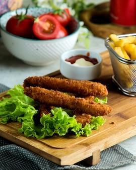 Vinger kipnuggets geserveerd met frietjes