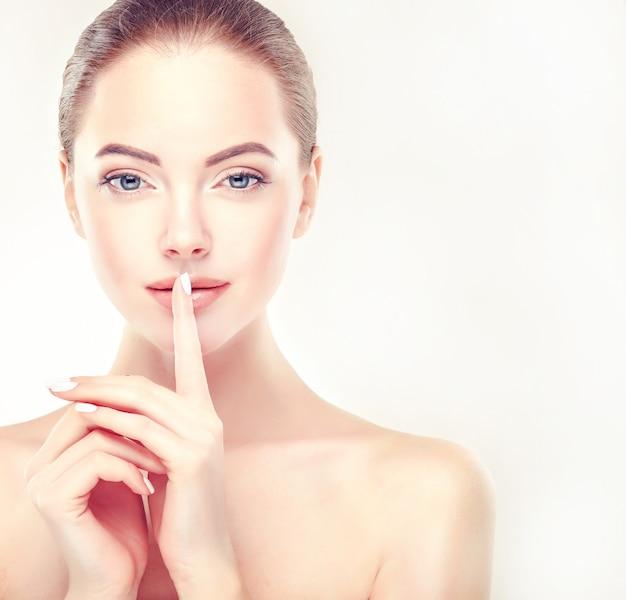 Vinger op de lippen mooi vrouwengezicht in een keurige make-up en een elegant gebaar van handen gezichtsverzorging