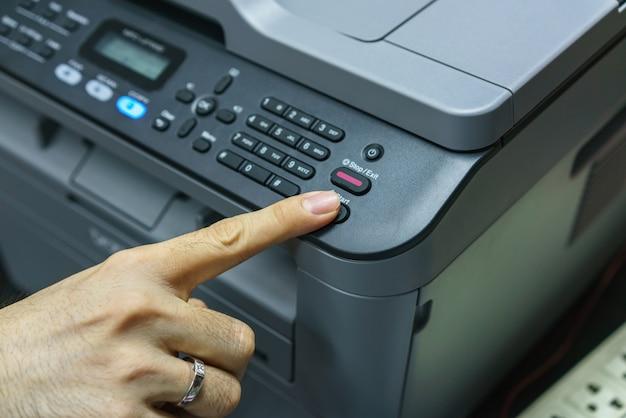 Vinger op startknop van faxapparaat, kantoorapparatuur