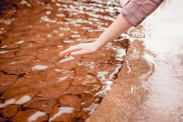 Vinger raakt water van dichtbij. zorg voor natuur, milieubescherming, gebrek aan drinkwater op de planeet. magisch contact tussen mens en natuur. milieuactiviteit. hand raakt het water aan.