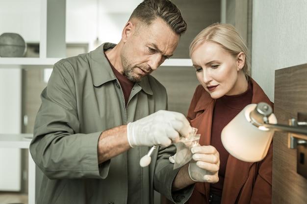 Vingerafdrukken onderzoeken. forensische wetenschappers bewaren sticker met vingerafdrukken in een plastic zak en sturen deze naar het criminele laboratorium