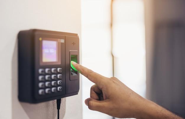 Vingerafdrukscan, mannelijke werknemers drukken op sensoren om de aanwezigheidstijd van het bedrijf en na het werk vast te leggen, tijdregistratie-aanwezigheid - buiten het werk, versleuteling voor identiteitsverificatie of elektronische ondertekening