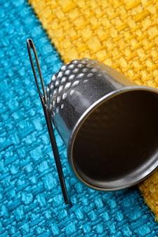 Vingerhoed en naainaald op geelblauwe stof. detailopname.