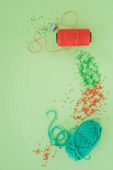 Vingerhoed; garen spoel; rode en groene kralen en wol op groene achtergrond