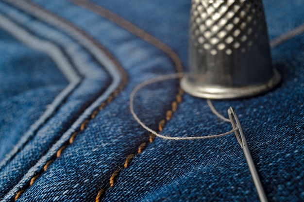 Vingerhoed, naai-naald met draad close-up op jeans.
