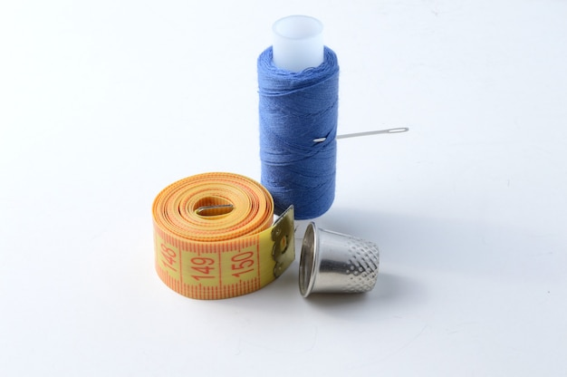 Vingerhoed, naald met draad en meetlint op een witte achtergrond .close-up.
