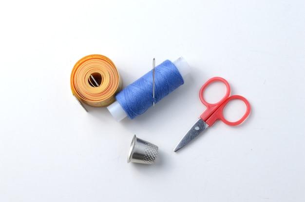 Vingerhoed, naald met spoel van draad, schaar en meetlint .close-up.