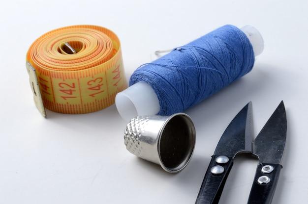 Vingerhoed, naald met spoel van draad, schaar en meetlint op een witte achtergrond .close-up.