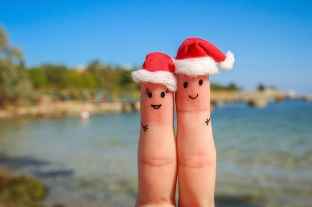 Vingerkunst van een gelukkig paar in kerstmutsen die op de zee rusten