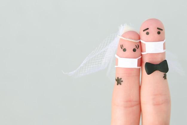 Vingerkunst van gelukkige paar in medische maskers bij huwelijksceremonie