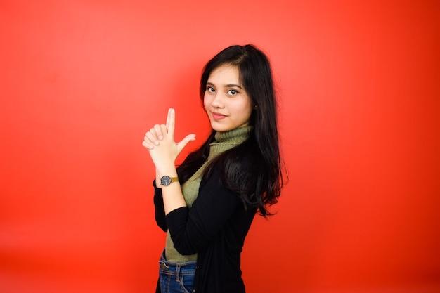 Vingerpistool of vingerpistool maken van jonge mooie aziatische vrouwen met zwarte trui geïsoleerd op re