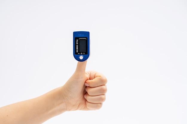 Vingerpulsoximeter. op witte achtergrond. het apparaat wordt met de duim omhoog gezet. gezondheidsdiagnostiek.