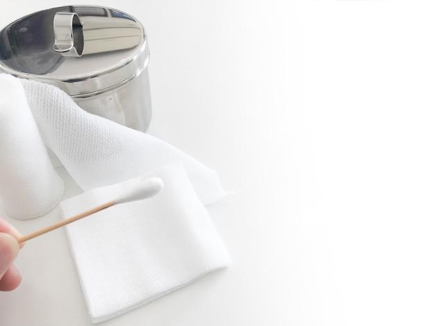 Vingerpunt houdt staafje met rolgaas en gaaspot met kopie ruimte vast