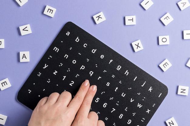 Vingers aanraken van braille-alfabetbord