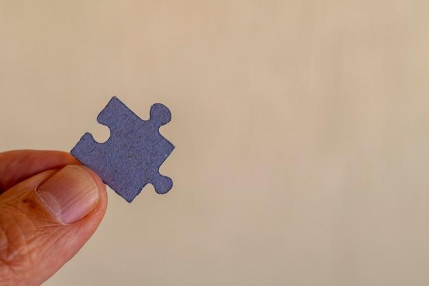 Vingers die een puzzelstukje vasthouden
