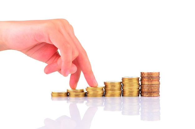 Vingers lopen op stapels munten op witte achtergrond. groei concept