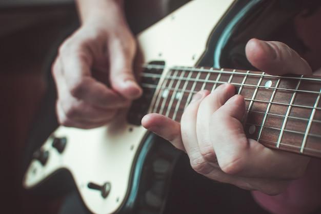 Vingers vormen een akkoord op een gitaar toets