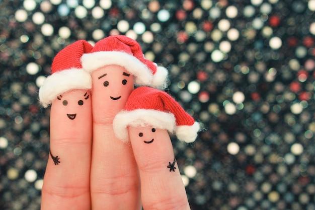 Vingerskunst van familie viert kerstmis. concept groep mensen glimlachen in nieuwe jaar hoeden.