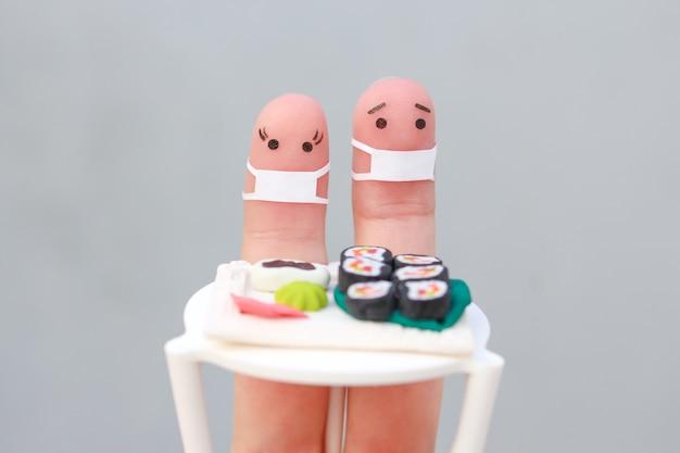 Vingerskunst van gelukkig paar met medisch masker van covid-2019. man en vrouw eten sushi in café.