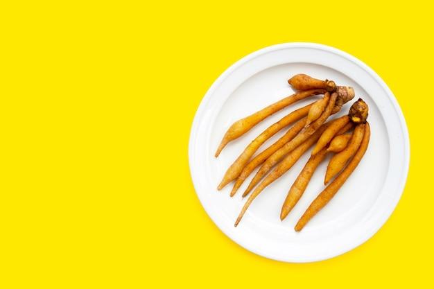 Vingerwortel in witte plaat op gele achtergrond.