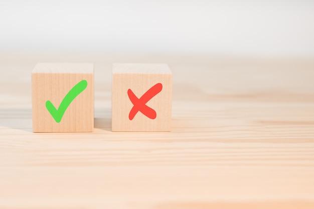 Vinkje en kruisje x op houten blokjes