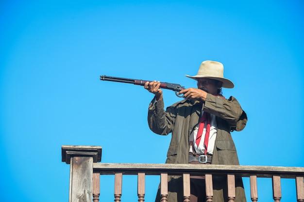 Vintage afbeelding van een cowboy die een geweer in zijn hand houdt, een leren hoed draagt, op het balkon van het huis staat, focus op het pistool en de cowboy