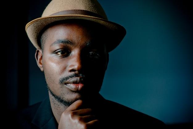 Vintage afrikaanse man zit in de donkere kamer, rustige stijl