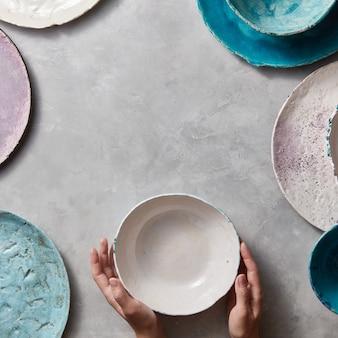 Vintage beschilderde borden schalen op grijze betonnen tafel met vrije ruimte ror tekst in het midden. het meisje houdt handwerkkom in haar hand. plat leggen.