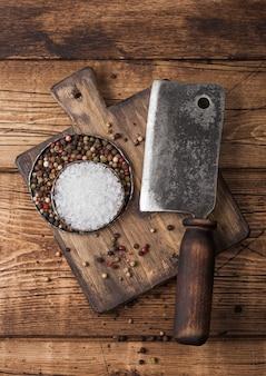 Vintage bijl voor vlees op houten snijplank met zout en peper op houten achtergrond.